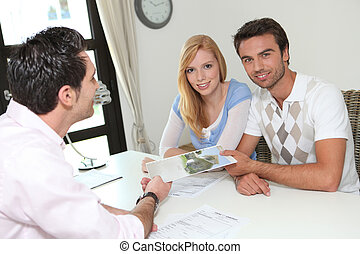 Young couple sat with estate agent