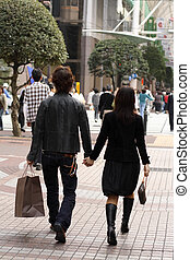 Young couple walking in a urban shopping area.