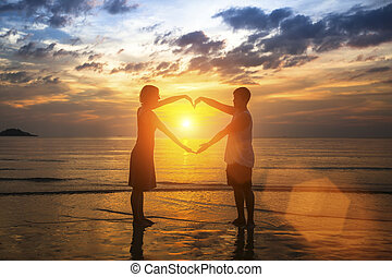 Young couple silhouette holding hands in heart shape on the beach at amazing sunset.
