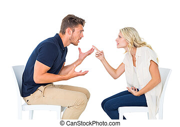 Young couple sitting in chairs arguing on white background