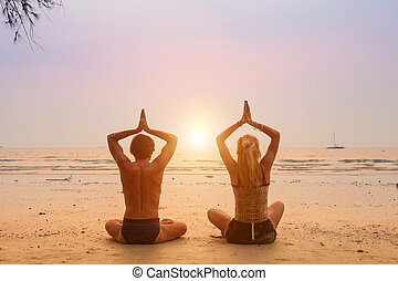 Young couple sitting on the beach of the sea in the lotus position at sunset.