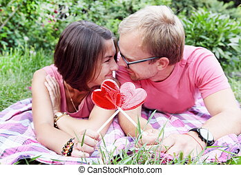 Young Couple with Candy Hearts on Picnic