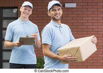 Young couriers with package and clipboard