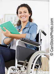 young disabled woman in wheelchair with book