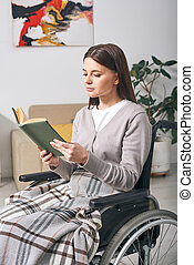 Young disabled woman reading book
