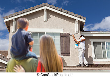 Young Family Watching House Get Painted by Painter