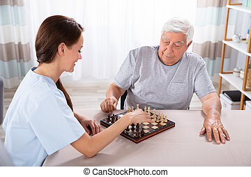 Female Caretaker Playing Chess With Senior Man