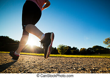Young fit woman does running, jogging training in a park at summer sunny day. Legs close up
