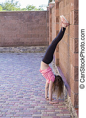 Young girl is standing upside down.