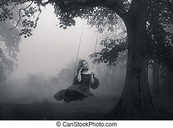 Young girl sitting on the swing