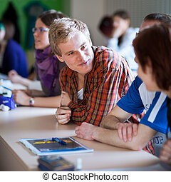 young, handsome college student sitting in a classroom