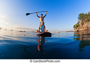 Young happy couple have fun on stand up paddleboard