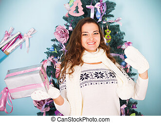 Young happy woman holding Christmas present