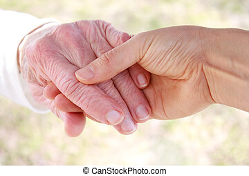 Young holding senior lady's hand outside