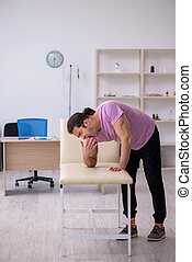 Young male patient waiting for doctor in the clinic