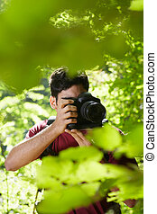 young hispanic man trekking among trees and taking pictures with dslr camera. Vertical shape, front view, copy space