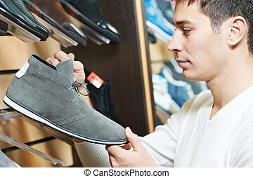 Young man choosing shoe in clothes store