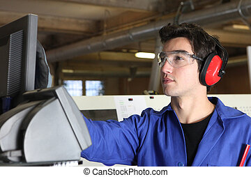 Young man operating machine in factory
