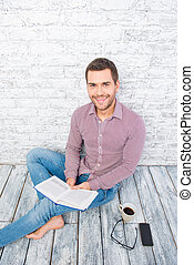 Young man sitting on the floor with book and cup of coffee