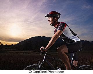 young man training on mountain bike at sunset