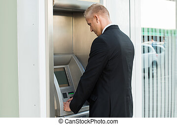 Young Man Using Atm Machine