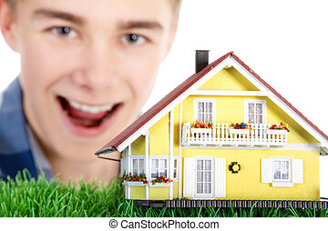 Young man with house laughs