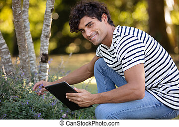 young man with tablet in the park