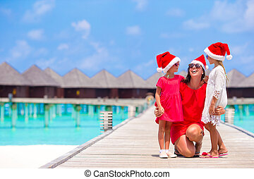 Young mother and little girls in Santa hat on Christmas holidays