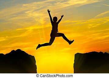 Silhouette of young person jumping over the mountains at sunset