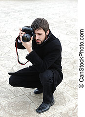 Young professional man with camera shooting outdoor