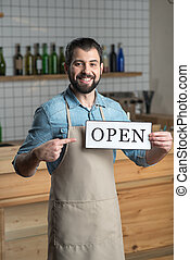 Young smart owner of a cafe showing the opening of this place