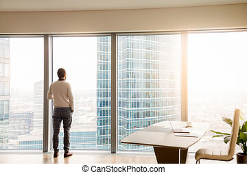 Young successful businessman standing in office looking at full-
