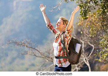 young woman arms open on top of the mountain