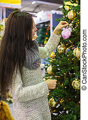 Young woman choosing decorations on the Christmas tree