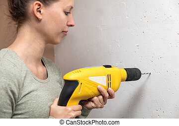 young woman drilled a hole in the wall