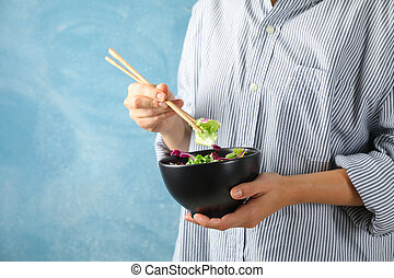 Young woman eat salad with chopsticks on blue background, space for text