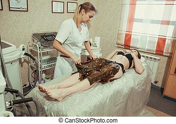 Young woman gets a treatment procedure algae in spa salon.