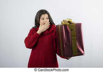 Young woman holding Christmas gift over white background