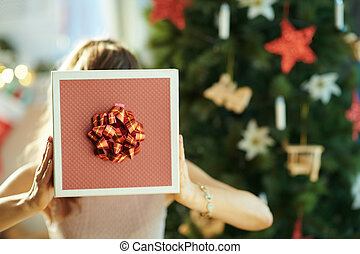 young woman holding Christmas present box in front of face