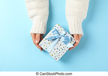 Young woman holding gift box on light blue background, space for text