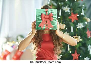 young woman holding green Christmas gift in front of face