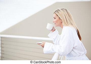 young woman in bathrobe drinking coffee