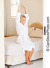 young woman in bathrobe stretching
