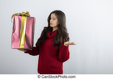 Young woman in red sweater looking at Christmas presents