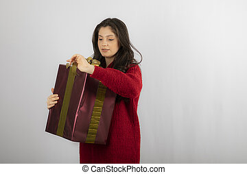 Young woman in red sweater opening a box of Christmas present