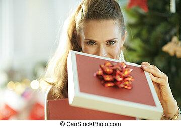 young woman near Christmas tree opening Christmas present box