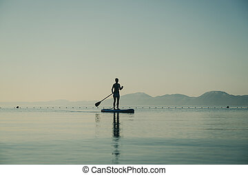 Young woman on stand up paddle board