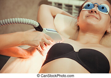 Young woman Receiving Laser Epilation Treatment On Underarms In Spa
