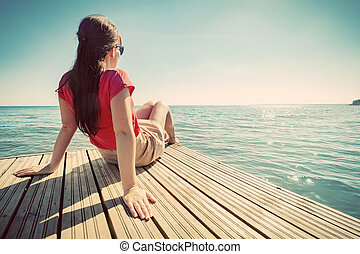 Young woman resting on jetty looking at the calm sea on sunny summer day.