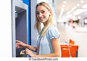 young woman stands on against atm in a shopping center